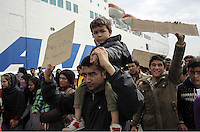 Pictured: Protesters march next to a ship Tuesday 08 March 2016<br /> Re: Afghan migrants hold a protest at Piraeus port, near Athens, Greece.