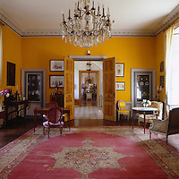The Grand Salon which has windows overlooking the garden is painted a deep yellow and was furnished through visits to various auctions