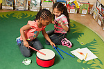 Education Preschool 3-4 year olds two girls playing musical instruments including drum together