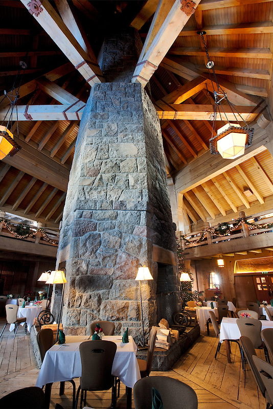 Dining area set for Christmas dinner and stone fireplace at Timberline Lodge. Oregon