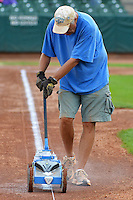 The grounds crew paints the lines on a soggy infield as the Ogden Raptors prepared to face the Grand Junction Rockies at Lindquist Field on September 8, 2013 in Ogden Utah.  (Stephen Smith/Four Seam Images)