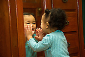 MR / Schenectady, NY. Toddler (1 year and 2 months old, African-American and Caucasian) exhibits one year old human development milestone behavior by showing strong interest in her own mirror image. She is making expressive faces in the mirror. MR: Dal4. ID: AM-HD. © Ellen B. Senisi