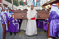 Antigua, Guatemala.  A Procession Monitor Guides a Float (Anda) forward as Young Boys Carry it in a Procession during Holy Week, La Semana Santa.  The lower half of an adult standing under the anda to help support it can be seen.