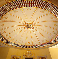 An oval shaped, domed ceiling decorated with hand-painted trees and carved and gilded rope