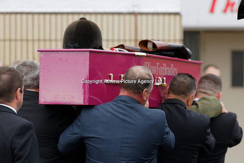 """Pictured: The coffin with Bradley's helmet, boots and whip are carried inside Aberavon Beach Hotel in Port Talbot, Wales, UK. Monday 08 October 218<br /> Re: A grieving father will mourners on horseback at the funeral of his """"wonderful"""" son who killed himself after being bullied at school.<br /> Talented young horse rider Bradley John, 14, was found hanged in the school toilets by his younger sister Danielle.<br /> Their father, farmer Byron John, 53, asked the local riding community to wear their smart hunting gear at Bradley's funeral.<br /> Police are investigating Bradley's death at the 500-pupils St John Lloyd Roman Catholic school in Llanelli, South Wales.<br /> Bradley's family claim he had been bullied for two years after being diagnosed with Attention Deficit Hyperactivity Disorder.<br /> He went missing during lessons and was found in the toilet cubicle by his sister Danielle, 12."""