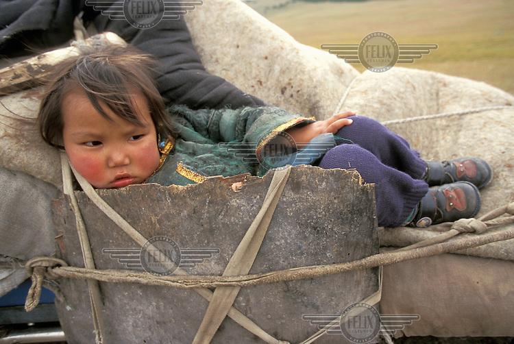 © Giacomo Pirozzi / Panos Pictures..Mongolia...Nomadic family on the move, a child sitting atop the wagon.