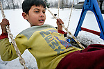Roma children, whose families were displaced by a severe cold spell, play on the swings at a temporary shelter established by the Red Cross in Smederevo, Serbia. Church World Service has provided affected families here with food and other emergency supplies.