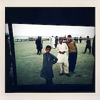 A group of young men stand on a piece of open land as seen through the window of a car.
