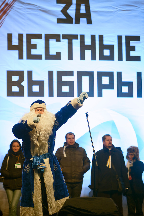 """Moscow, Russia, 24/12/2011..A protestor dressed as Ded Moroz, or Father Frost, onstage in front of a banner that reads """"For Honest Elections"""". An estimated crowd of up to 100,000 protested against election fraud and Prime Minister Vladimir Putin in the largest anti-government demonstration in Russia since the collapse of the Soviet Union."""