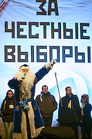 "Moscow, Russia, 24/12/2011..A protestor dressed as Ded Moroz, or Father Frost, onstage in front of a banner that reads ""For Honest Elections"". An estimated crowd of up to 100,000 protested against election fraud and Prime Minister Vladimir Putin in the largest anti-government demonstration in Russia since the collapse of the Soviet Union."