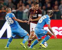 Calcio, Serie A: Roma vs Napoli. Roma, stadio Olimpico, 18 ottobre 2013.<br /> AS Roma forward Francesco Totti, center, is challenged by Napoli midfielders Gokhan Inler, of Switzerland, left, and Valon Behrami, of Switzerland, during the Italian Serie A football match between AS Roma and Napoli at Rome's Olympic stadium, 18 October 2013.<br /> UPDATE IMAGES PRESS/Riccardo De Luca