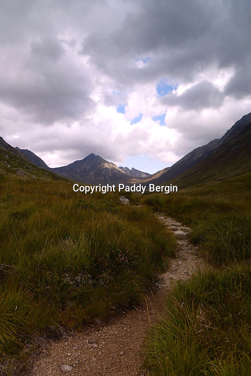 Path in Glen Rosa (Scottish Gaelic: Gleann Ruasaidh) is a glen near Goat Fell on the Isle of Arran in the Firth of Clyde, western Scotland.<br /> <br /> Glen Rosa can be reached from the road just outside Brodick. The trek up the glen is fairly low-lying, gaining less than 200 metres (660 feet) in altitude. This is a walk anyone can do, at least in good weather.<br /> <br /> Stock Photo by Paddy Bergin