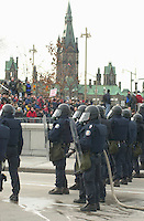 OTTAWA , November 17th 2001 FILE PHOTO<br /> <br />  Policemen in riot gear stand guard the security perimeter while demonstrators gathers on the other side of the barricades, during the Summit of G-20 Countries in Ottawa on Saturday, November 17, 2001.<br /> <br />  Police  used tear gas, concussion grenade's and pepper spray in their attempt to repel the protestor's from entering the security perimeter.<br /> <br /> The  G-20 meeting , where central bank chiefs and finance ministers from rich and poor nations discuss topics such as ; terrorism funding, economy slowdown and 3rd world nation's debt was initially scheduled for september in India,but  postponed  to  November 16th to 18th, 2001 and is beeing hosted by G-20 Chair ;  Canada Minister of Finance ;  Paul Martin.