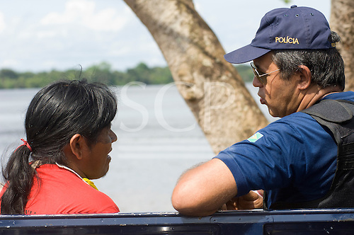 """Altamira, Brazil. """"Xingu Vivo Para Sempre"""" protest meeting about the proposed Belo Monte hydroeletric dam and other dams on the Xingu river and its tributaries. A policeman chats to  a Kayapo Indian."""