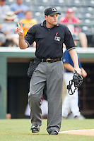 Home plate umpire Johnny Conrad calls for 2 baseballs during an International League game between the Toledo Mudhens and the Charlotte Knights at Knights Stadium August 8, 2010, in Fort Mill, South Carolina.  Photo by Brian Westerholt / Four Seam Images
