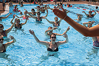 Switzerland. Canton Ticino. Tenero. Camping Campofelice. Campers enjoy an hour of water aerobics in the swimming pool. Water aerobics (waterobics, aquatic fitness, aquafitness, aquafit) is the performance of aerobic exercise in fairly shallow water such as in a swimming pool. Done mostly vertically and without swimming typically in waist deep or deeper water, it is a type of resistance training. Water aerobics is a form of aerobic exercise that requires water-immersed participants. Most water aerobics is in a group fitness class setting with a trained professional teaching for about an hour. The classes focus on aerobic endurance, resistance training, and creating an enjoyable atmosphere with music. 20.07.2018 © 2018 Didier Ruef