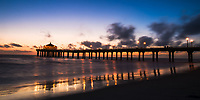 Colorful sunset on the famous Manhattan Beach pier and Roundhouse Aquarium, reflecting on the Pacific Ocean and wet sand, Los Angeles California USA
