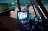 Cowboy sitting in his pickup truck checking out the internet on his laptop computer.
