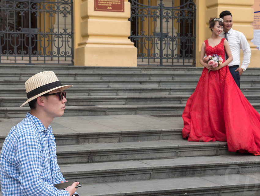 People and everyday life in the streets of Hanoi, Vietnam. A strange scene; a wedding photographer, a tourist and the wedding couple outside the Opera House in Hanoi.