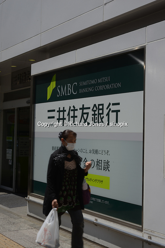 A woman is passing in front of Japanese bank, Mitsui Sumitomo bank in Tachikawa, Tokyo, Japan.
