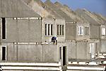UTRECHT - Een niet aangelijnde bouwvakker zonder valbeveiliging werkt aan het betonnen casco van een woningbouwproject bestaande uit eengezinswoningen. COPYRIGHT TON BORSBOOM