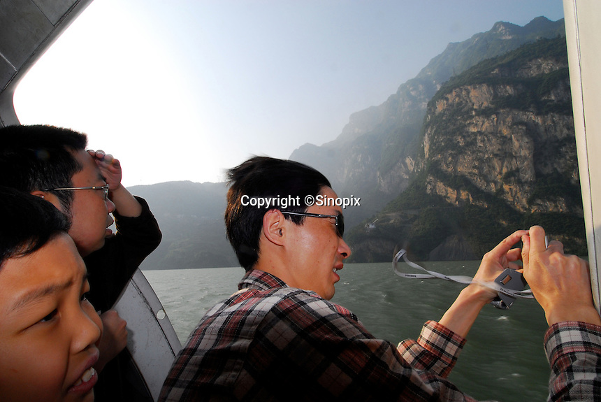 """Tourists look at the Wu Gorge from the window of a hydrofoil whilst travelling up the Newly formed """"ribbon lake"""" of the Yangtze River in China. The construction of the Three Gorges Dam and rise in water level of around 100 meters, creating a narrow lake 450 km in length and  has resulted in the relocation of around 1.5 million people. All of their homes have been destroyed. The Dam is now completed and the water will rise a further 35 meters this fall..16 May 2006"""