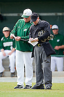 Charlotte 49ers head coach Loren Hibbs #49 goes over lineup changes with home plate umpire Brian Kennedy between innings of the game against the Saint Peter's Peacocks at Robert and Mariam Hayes Stadium on February 18, 2012 in Charlotte, North Carolina.  Brian Westerholt / Four Seam Images