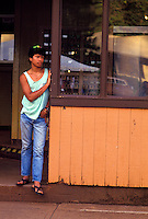 Young man resting against the side of a building in Lanai city, Lanai