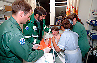Paramedic ambulance crew have brought a child with a broken arm into the A&E department of a hospital. The child has been transported to hospital in an ambulance wearing a removable splint, which the nurse is now helping to remove. This image may only be used to portray the subject in a positive manner..©shoutpictures.com..john@shoutpictures.com