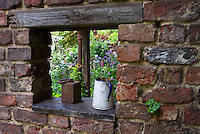 Framing a garden view: Making a hole in a brick wall to create a secret garden window. Rustic antiques and lush flower plantings