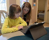 Katie Presley, 11, shows her mother, Jacqueline Presley, her progress Thursday, Sept. 10, 2020, while completing school work in their home in Springdale. Katie and her brother, Jackson Presley, 9, are enrolled in the Springdale School District's Virtual Innovation Academy in the Don Tyson School of Innovation. Visit nwaonline.com/200913Daily/ for today's photo gallery. <br /> (NWA Democrat-Gazette/Andy Shupe)