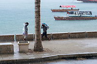 TANZANIA, Zanzibar, Stone town, raining day at port, two boys in rain