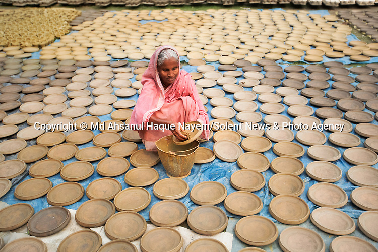 Workers create thousands of golden clay pots and leaving them out to dry in the sun.  Around 3,000 of the pots are made here on a daily basis using a unique yellow soil.<br /> <br /> This natural colouring is part of a traditional process done only by the people of the Pal community of Hinduism in Bogra, Bangladesh.  SEE OUR COPY FOR DETAILS.<br /> <br /> Please byline: Md Ahsanul Haque Nayem/Solent News<br /> <br /> © Md Ahsanul Haque Nayem/Solent News & Photo Agency<br /> UK +44 (0) 2380 458800