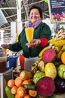 Peru, Cusco, San Pedro Market.  Juice Vendor Preparing Mango Juice.