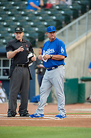 Home plate umpire Brian Walsh talks to Tulsa Drillers manager Scott Hennessey (46) on May 13, 2019, at Arvest Ballpark in Springdale, Arkansas. (Jason Ivester/Four Seam Images)