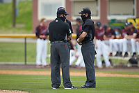 (L-R) The umpiring crew of Mike Mackey, De'Andre Anderson, and Jerry Buresh discuss a call during the NCAA bseball game between the North Carolina A&T Aggies and the North Carolina Central Eagles at Durham Athletic Park on April 10, 2021 in Durham, North Carolina. (Brian Westerholt/Four Seam Images)