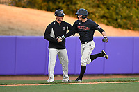 Shortstop Buddy Mrowka (5) of the Harvard Crimson is congratulated by the third base coach after hitting a home run in game two of a doubleheader against the Furman Paladins on Friday, March 16, 2018, at Latham Baseball Stadium on the Furman University campus in Greenville, South Carolina. Furman won, 7-6. (Tom Priddy/Four Seam Images)
