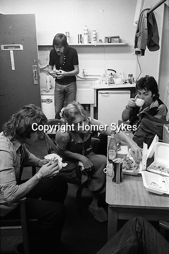 "Paul and Linda McCartney Wings Tour 1975. Paul, Linda and Denny Laine tuck into a fast food take away fish and chips meal,  Elstree rehearsal studio London,  England. The photographs from this set were taken in 1975. I was on tour with them for a children's ""Fact Book"". This book was called, The Facts about a Pop Group Featuring Wings. Introduced by Paul McCartney, published by G.Whizzard. They had recently recorded albums, Wildlife, Red Rose Speedway, Band on the Run and Venus and Mars. I believe it was the English leg of Wings Over the World tour. But as I recall they were promoting,  Band on the Run and Venus and Mars in particular."