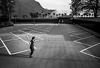 """Switzerland. Canton Ticino. Lugano. Family game. A father and his daughter play tennis. The empty parking lot is located near near the tennis courts and the swimming pool. No cars. Due to the spread of the coronavirus (also called Covid-19, the Federal Council has categorised the situation in the country as """"extraordinary"""". It has issued a recommendation to all citizens to stay at home, especially the sick and the elderly. From March 16 the government ramped up its response to the widening pandemic, ordering the closure of bars, restaurants, sports facilities and cultural spaces. Only businesses providing essential goods to the population – such as grocery stores, bakeries and pharmacies – are to remain open. 13.04.2020 © 2020 Didier Ruef"""