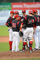 Batavia Muckdogs pitching coach Brendan Sagara (28) talks with pitcher Ryan Newell (center) as Justin Bohn, Javier Lopez, Chad Wallach and Felix Munoz list in during a game against the Tri-City ValleyCats on July 13, 2013 at Dwyer Stadium in Batavia, New York.  Tri-City defeated Batavia 5-4.  (Mike Janes/Four Seam Images)