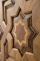 A detail of the decorative star shaped wood inlay of a heavy mahoghany front door