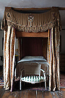 This Jacobean four-poster bed is draped in antique bed hangings embroidered with coats of arms