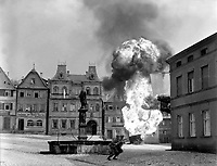 Two anti-tank Infantrymen of the 101st Infantry Regiment, dash past a blazing German gasoline trailer in square of Kronach, Germany.  April 14, 1945.  T4c.  W.J. Rothenberger.  (Army)<br /> NARA FILE #:  111-SC-206235<br /> WAR & CONFLICT BOOK #:  1091