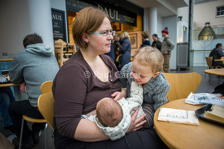 A mother breastfeeding her baby  in a museum cafe while the older sybling tries to play with the baby.<br /> <br /> London, England, UK<br /> 08/03/2015<br /> <br /> © Paul Carter / wdiip.co.uk