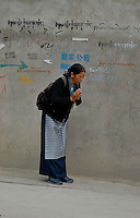 Praying and walking in one of the side streets in Lhasa towards the temple, Lhasa Tibet
