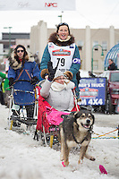 Zoya DeNure and team leave the ceremonial start line with an Iditarider at 4th Avenue and D street in downtown Anchorage, Alaska during the 2015 Iditarod race. Photo by Jim Kohl/IditarodPhotos.com
