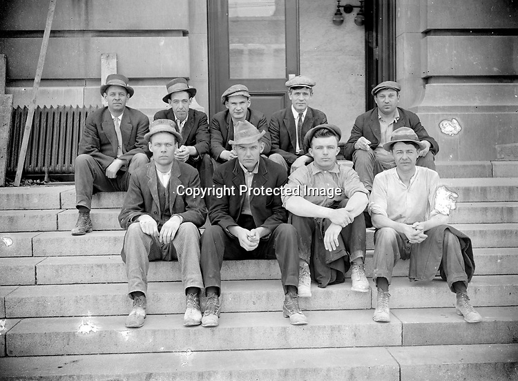 WORKMEN AT THE POST OFFICE, C. 1915. Nine more workmen pose in front of a half-open door, showing a light fixture inside. While most of the men wear coats and a few wear ties, their well-worn boots and mix of caps and hats suggests that these are not office workers. The steam radiator at left was removed during the remodeling and awaits reinstallation.<br /> <br /> Photographs taken on black and white glass negatives by African American photographer(s) John Johnson and Earl McWilliams from 1910 to 1925 in Lincoln, Nebraska. Douglas Keister has 280 5x7 glass negatives taken by these photographers. Larger scans available on request.