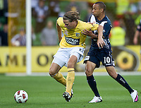 MELBOURNE, AUSTRALIA - NOVEMBER 18: Archie Thompson of the Victory challenges Patrick Zwaanswijk of the Mariners during the round 14 A-League match between the Melbourne Victory and Central Coast Mariners at AAMI Park on November 18, 2010 in Melbourne, Australia (Photo by Sydney Low / Asterisk Images)