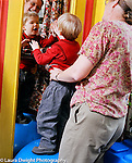 Occupational Therapy therapist at work with 2 year old boy balanced on ball looking at own reflection in mirror vertical