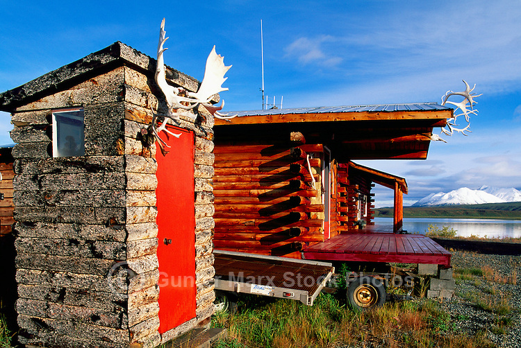 Rustic Outhouse / Outside Toilet / Outdoor Loo with Moose Antlers hanging over a Red Door, and Log Cabin at Summit Lake, Alaska, USA